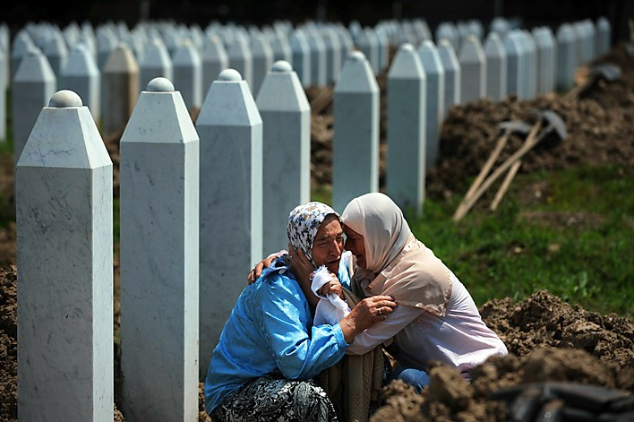 Bosnian women cry at the grave of a rela